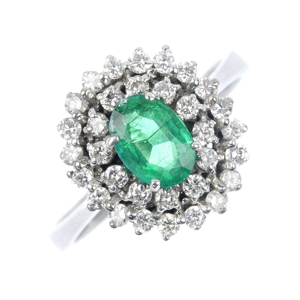 10: An 18ct gold emerald and diamond cluster ring.