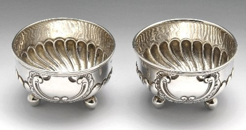 A pair of silver salts, a shell dish, butter knife and