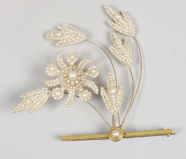 3: A single pearl bar brooch supporting a flo