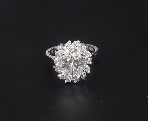 654: Oval diamond cluster ring - a central ov