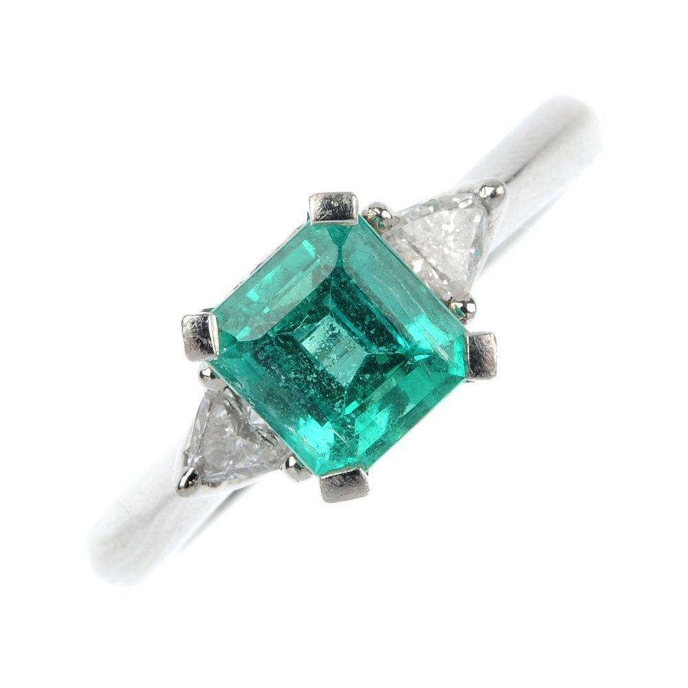 A platinum emerald and diamond dress ring.