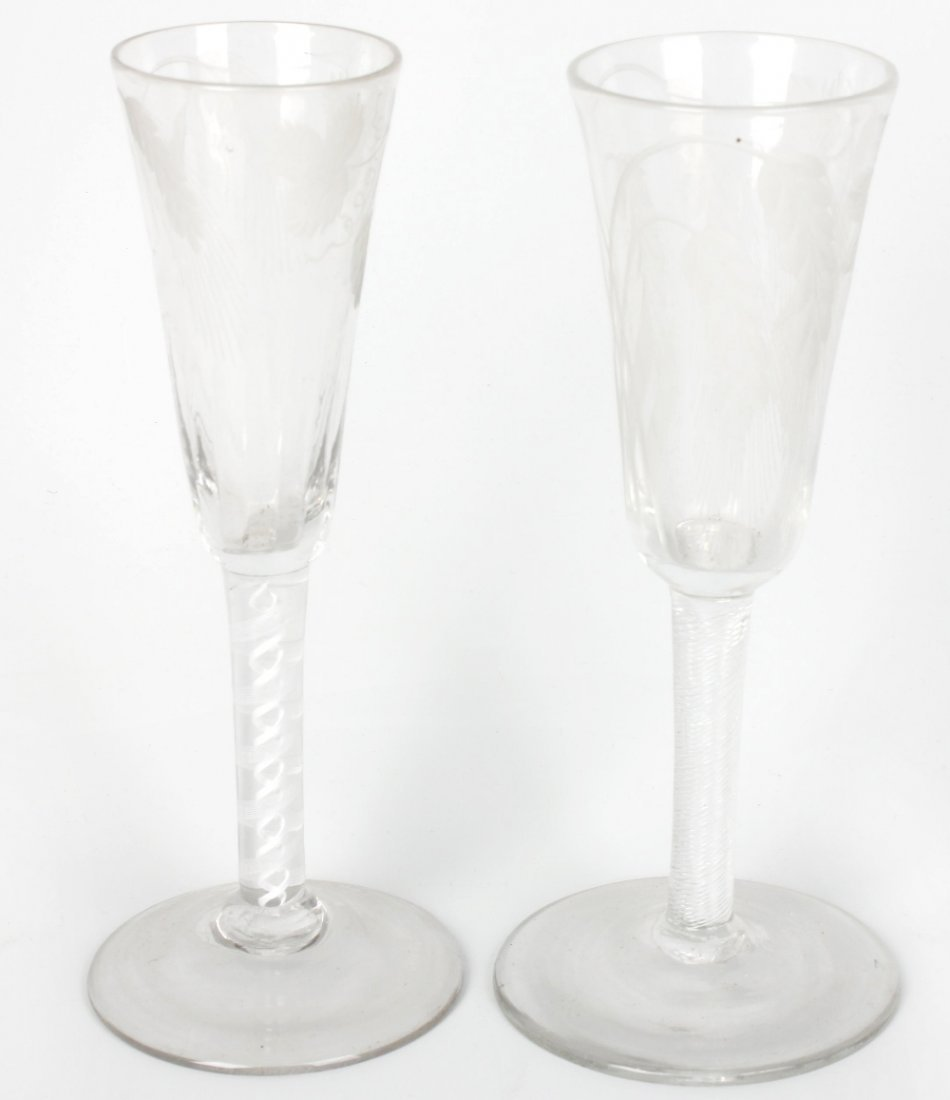 A glass with flared conical shaped bowl and a similar e