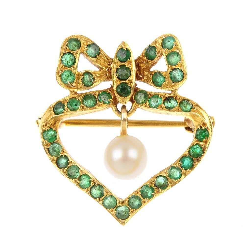 An emerald and diamond brooch.