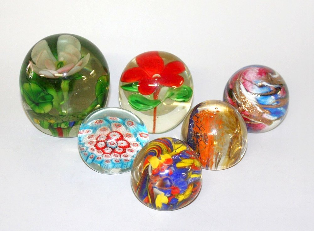 Twenty four assorted glass paperweights