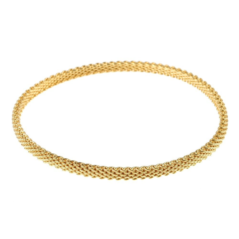 TIFFANY & CO. - an 18ct gold mesh bangle.