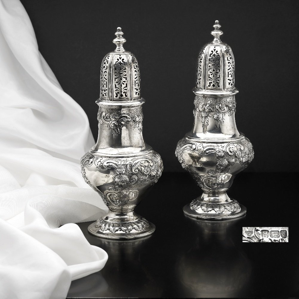 A pair of George III large silver casters.