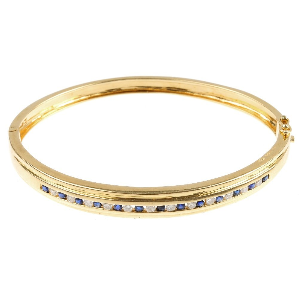 An 18ct gold sapphire and diamond hinged bangle.