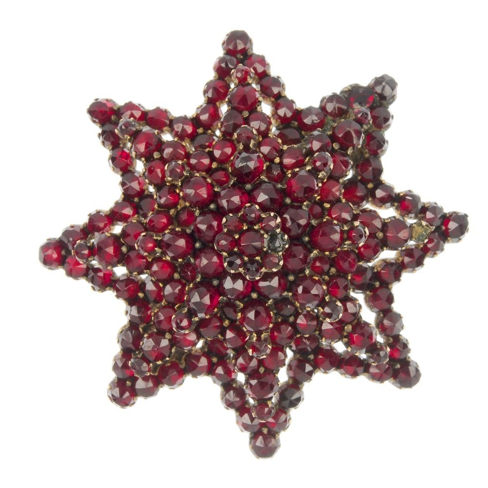 A late 19th century red paste star brooch.