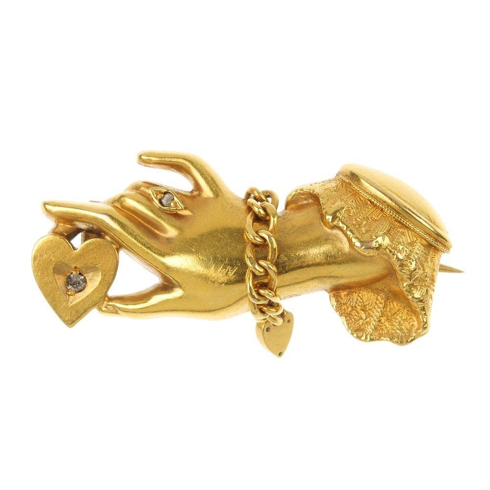 An Edwardian 15ct gold diamond hand brooch.