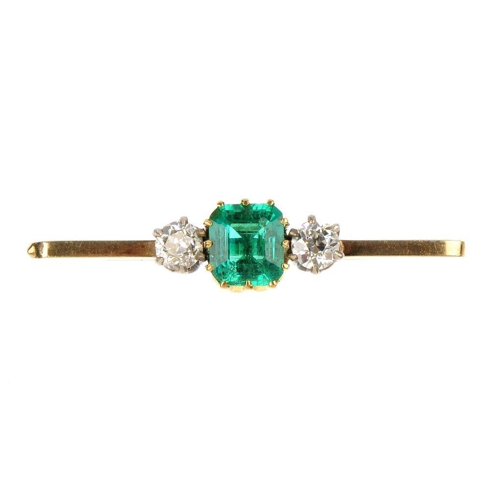 An emerald and diamond three-stone brooch.