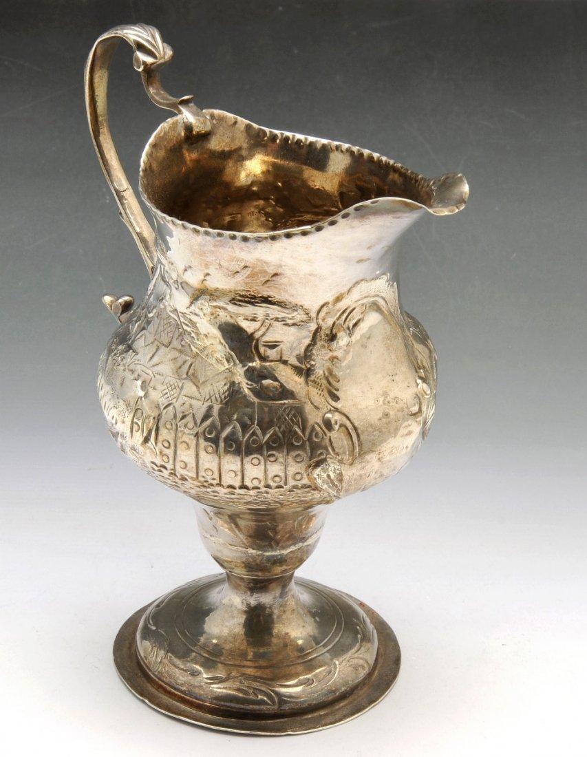 A George III silver cream jug.