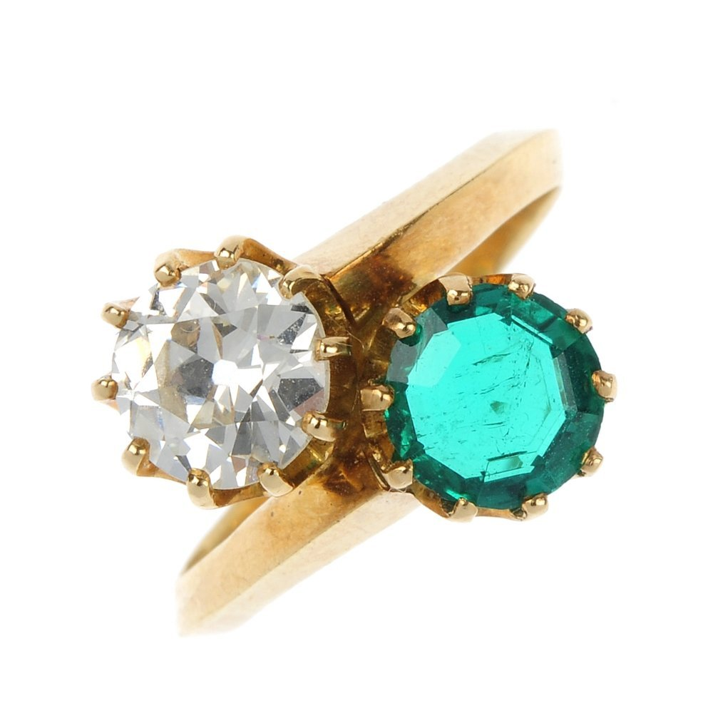 An emerald and diamond two-stone crossover ring.