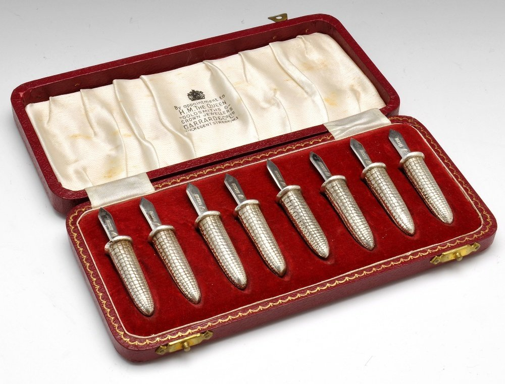 A cased set of corn cob holders.