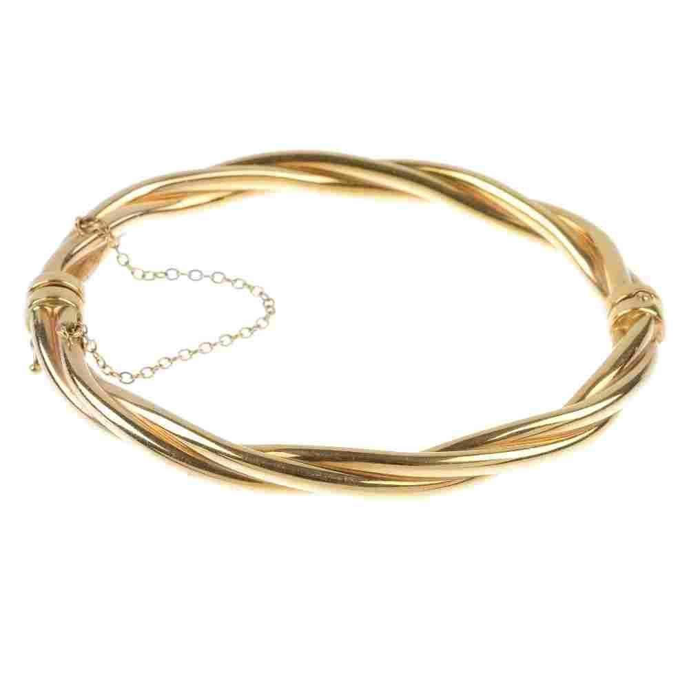 A 9ct gold hinged bangle.