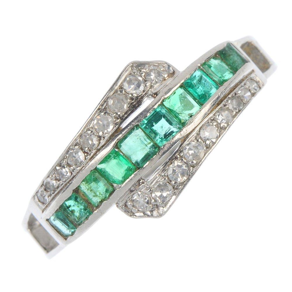 A platinum emerald and diamond ring.