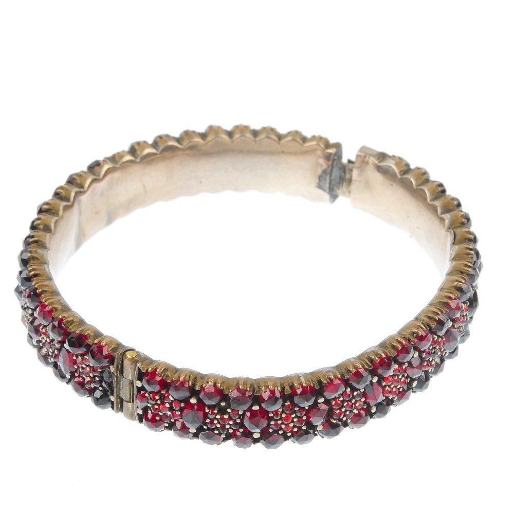 A late 19th century garnet and paste bangle and a 9ct