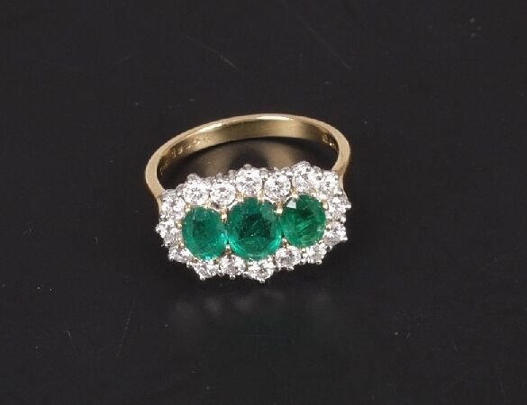 11: 18ct gold oval emerald and diamond triple