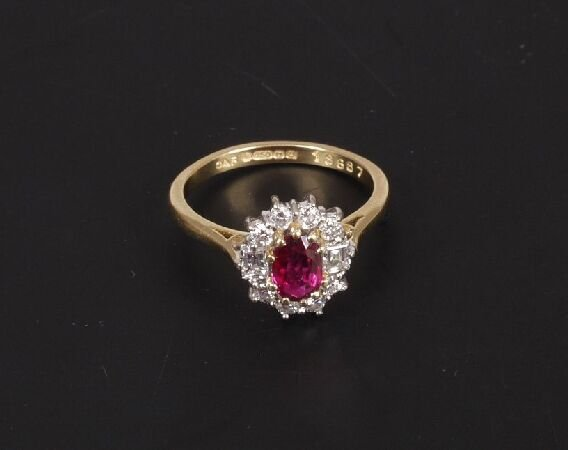12: 18ct gold oval ruby and diamond cluster r
