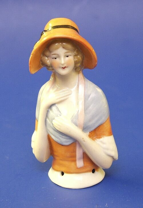 9: A porcelain half doll modelled as a young