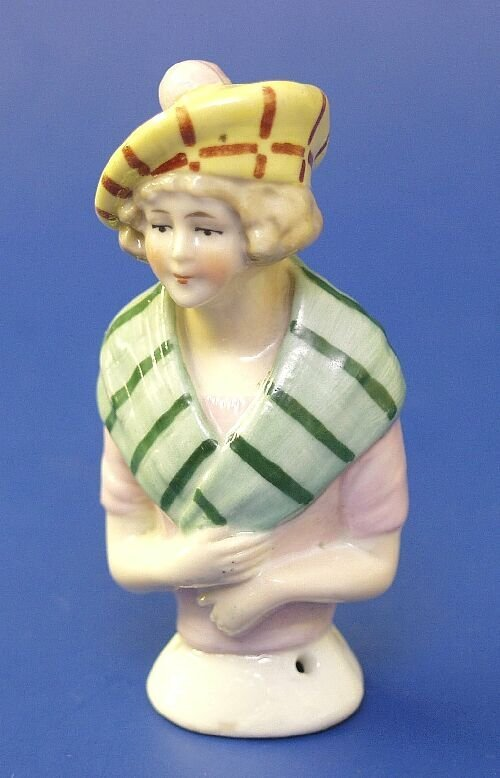 11: A porcelain half doll modelled as a young