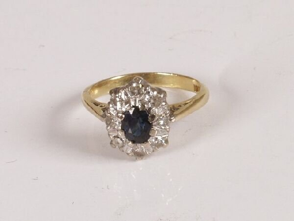22: Yellow metal oval sapphire and diamond cluster ring