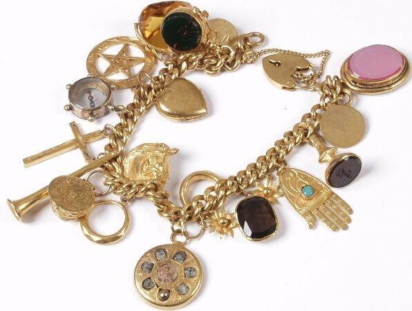 24: 9ct gold charm bracelet suspending twenty charms in