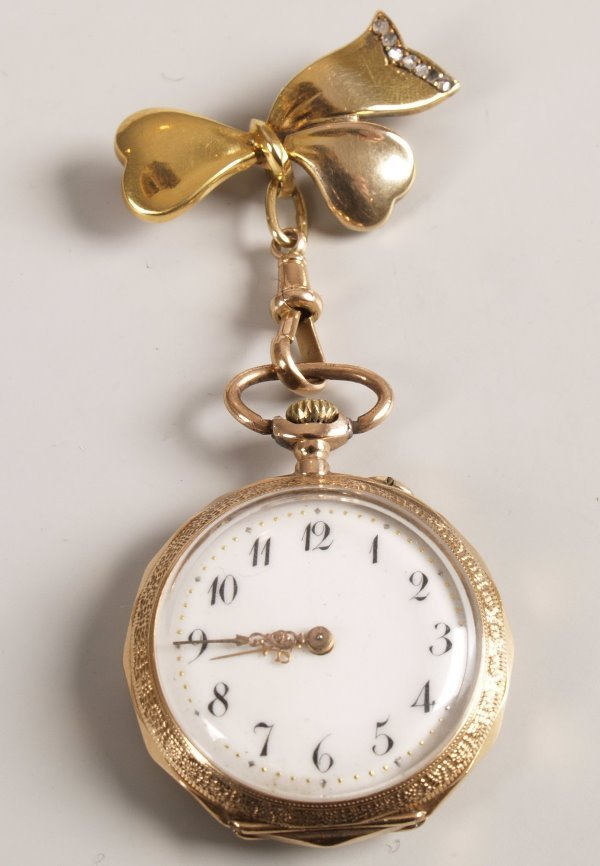 21: 14ct gold top wind fob watch with a white face and