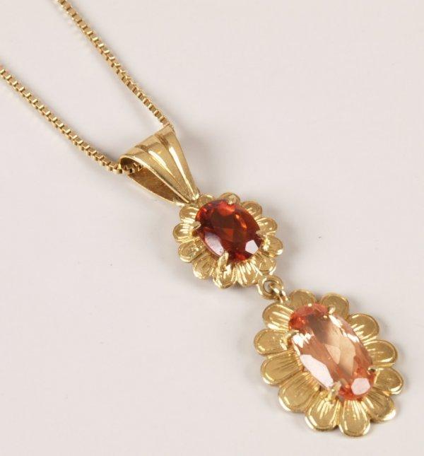 7: 18ct gold gem set pendant with an oval orange stone