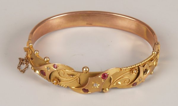 10: Edwardian 9ct gold ruby and diamond bangle with thr