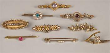 776 A collection of nine brooches to include a 15ct go