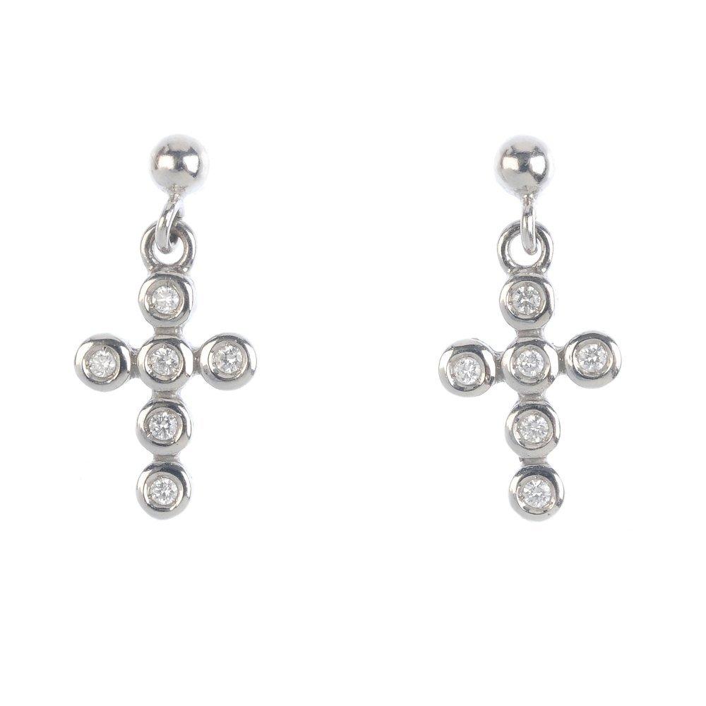 A pair of diamond cross earrings. Each designed as a