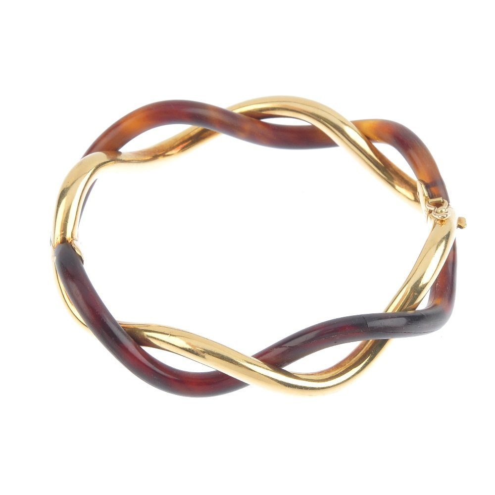 (545050-2-A) An 18ct gold and horn hinged bangle.