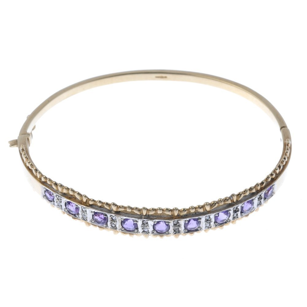 A 9ct gold amethyst and diamond bangle. Designed as a