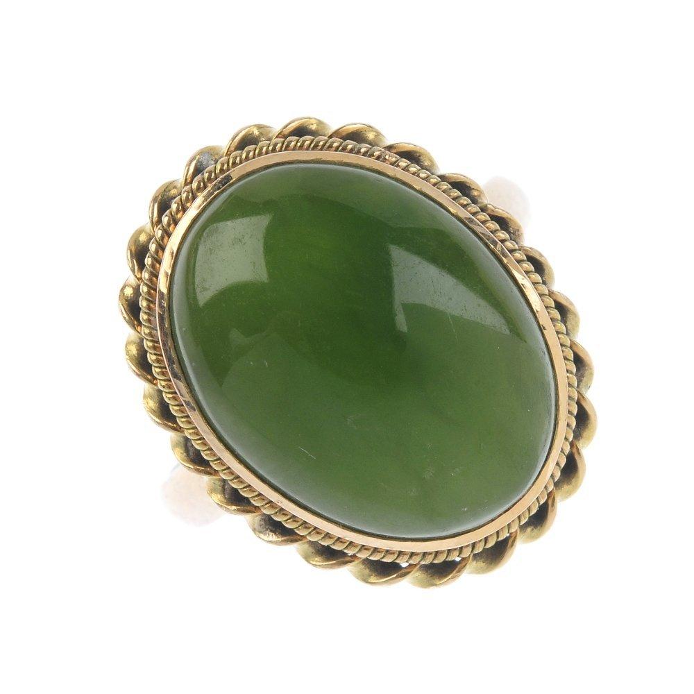 A jade single-stone ring. The oval jade cabochon,