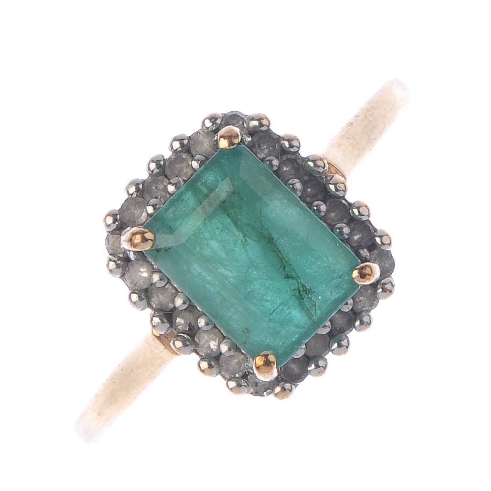 A 9ct gold emerald and diamond cluster ring. The