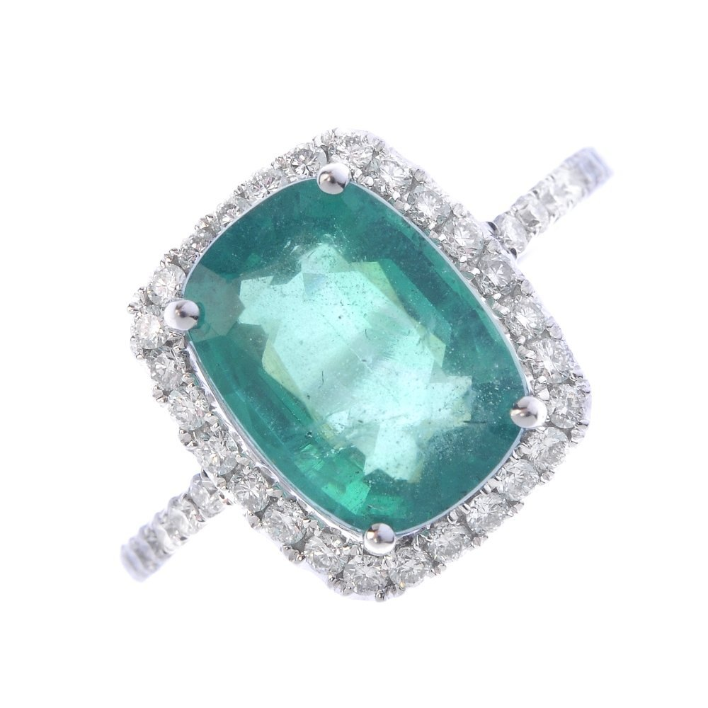 An emerald and diamond cluster ring. The cushion-shape