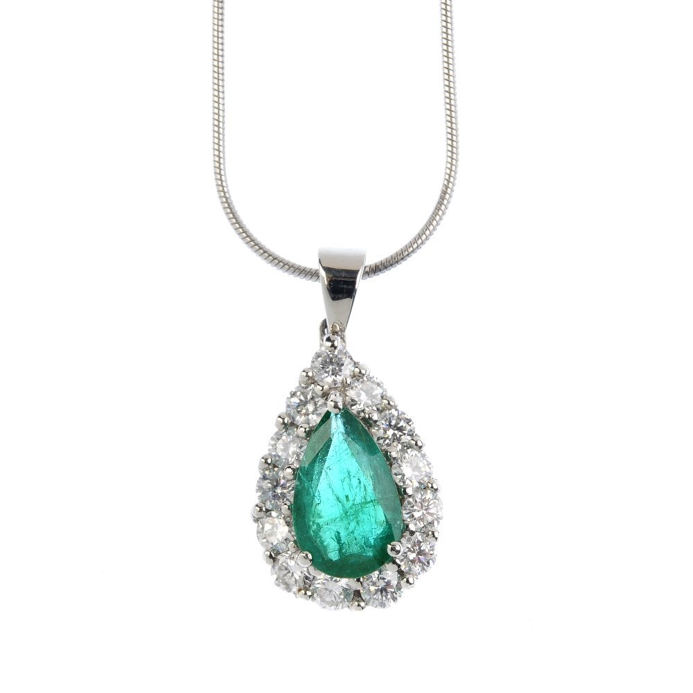 A platinum, emerald and diamond cluster pendant. The