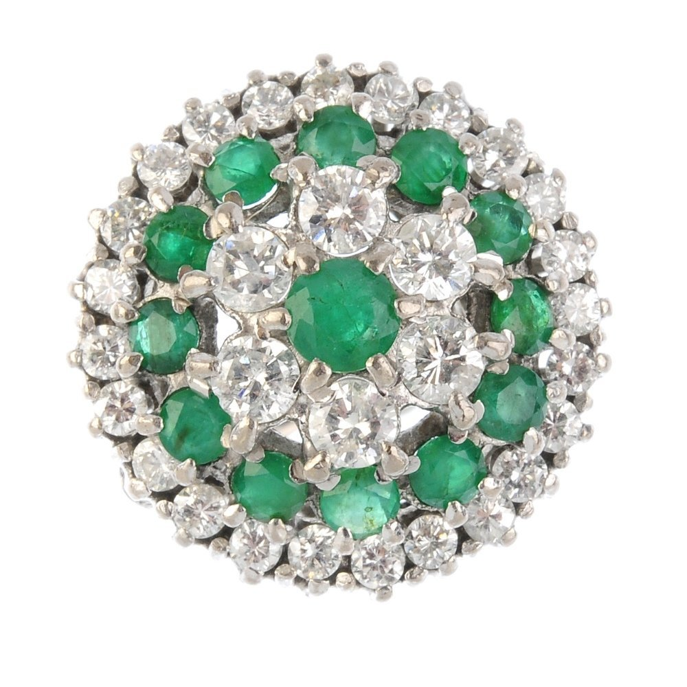 An 18ct gold diamond and emerald cluster ring. The