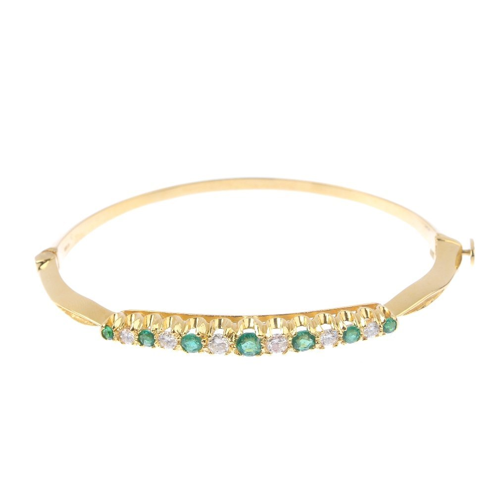 An 18ct gold emerald and diamond hinged bangle.