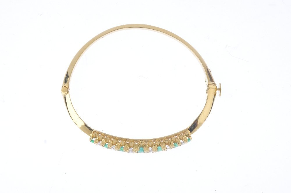 An 18ct gold emerald and diamond hinged bangle. - 2