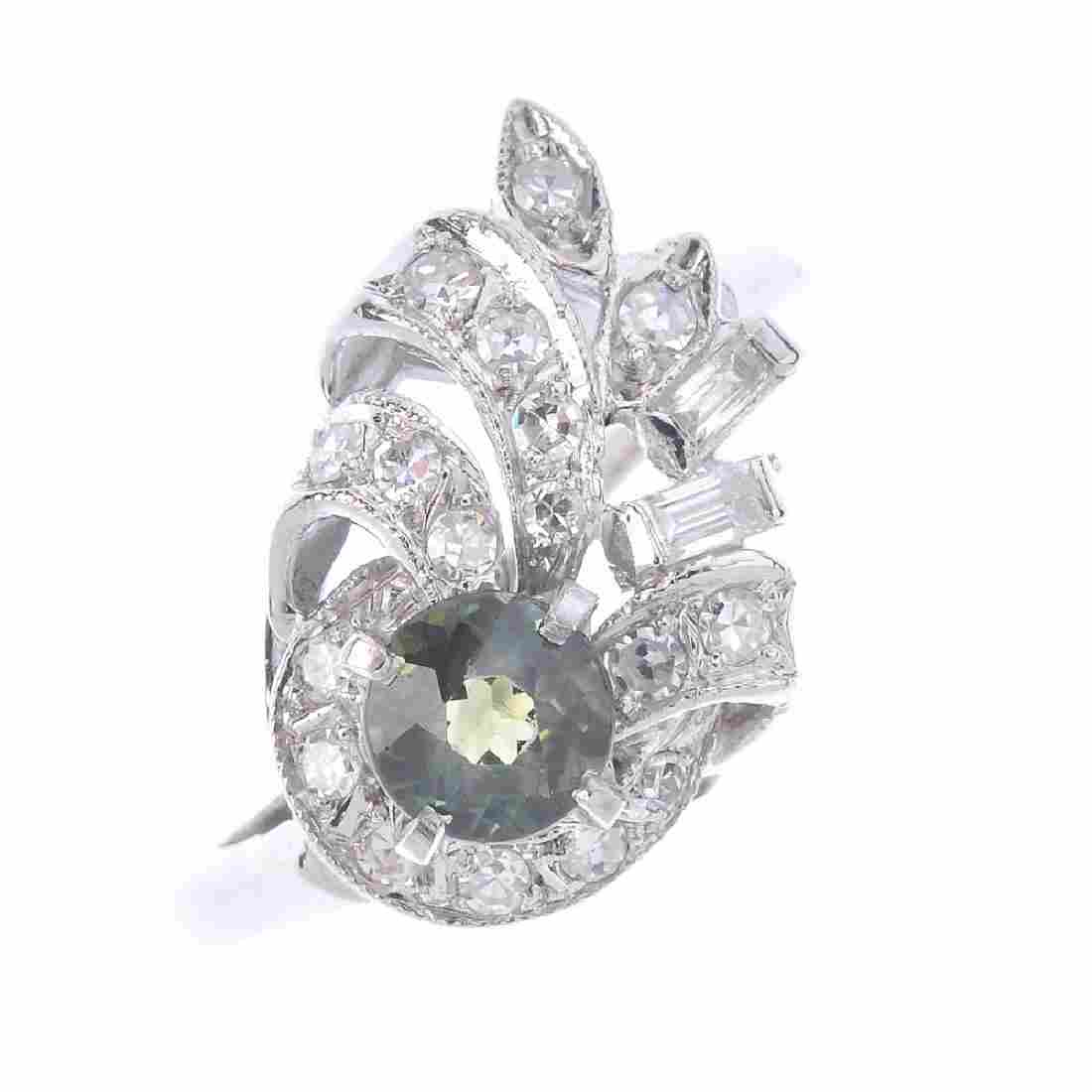 A diamond and sapphire dress ring. Of abstract design,