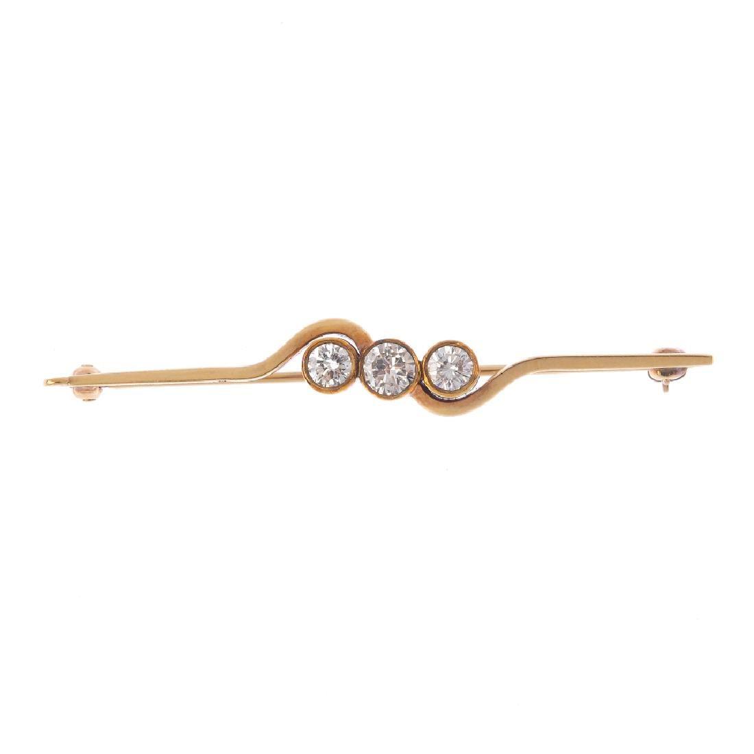 A 9ct gold diamond three-stone bar brooch. The