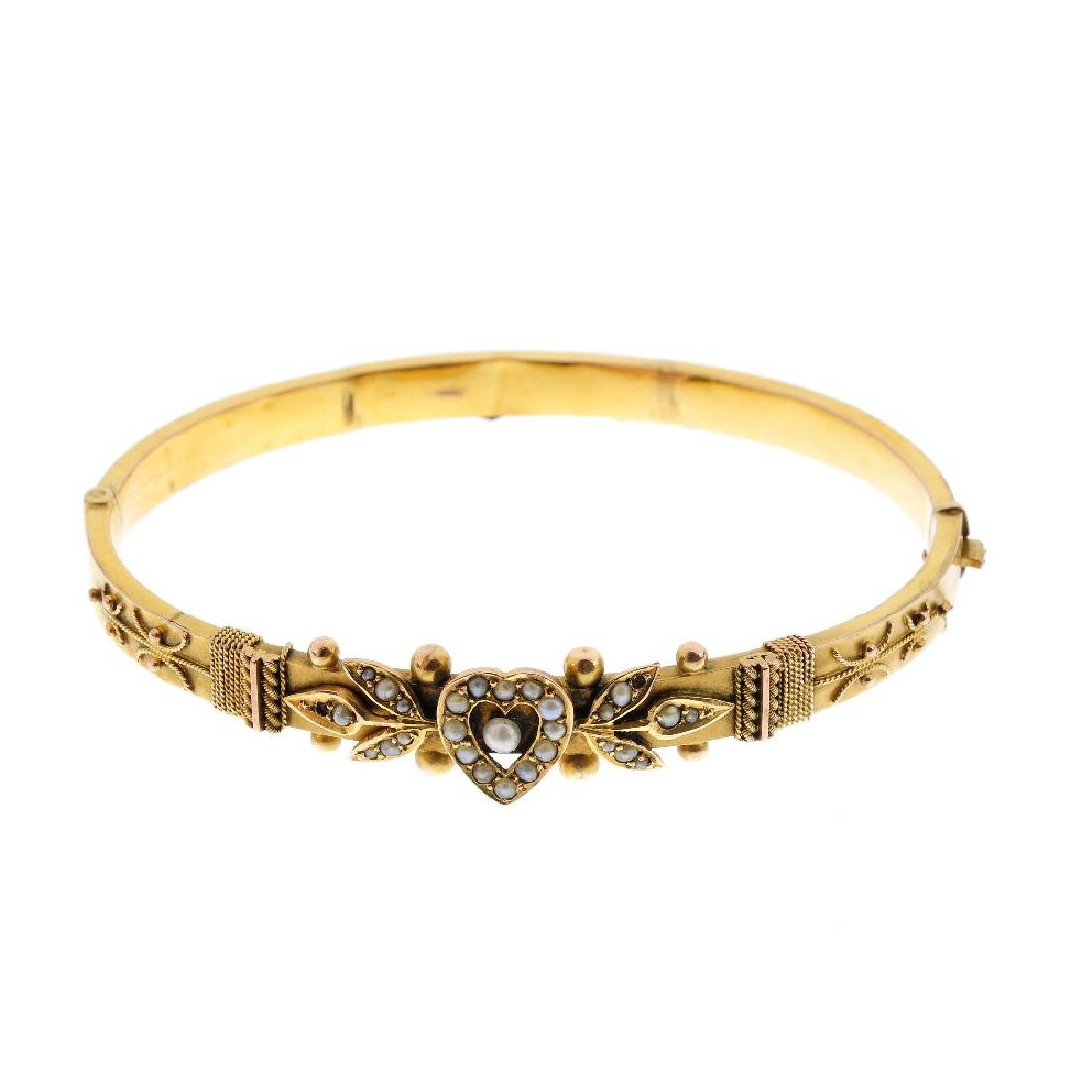 An Edwardian 9ct gold split pearl hinged bangle. The