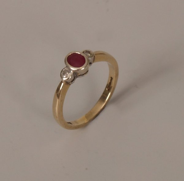 23: 9ct gold three stone ruby and diamond ring, with a