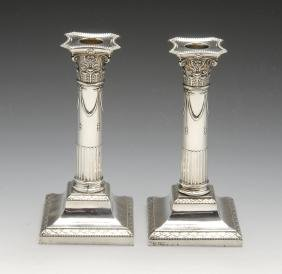 A pair of Edwardian silver mounted candlesticks, the