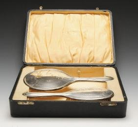 A 1920's cased silver mounted hand mirror and hairbrush