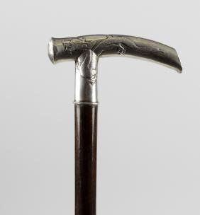 A 19th century white metal handled walking cane, the
