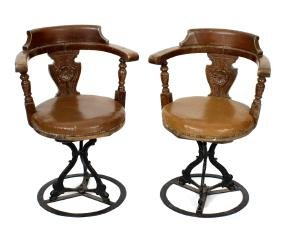 A pair of folding stained wooden x frame chairs, with