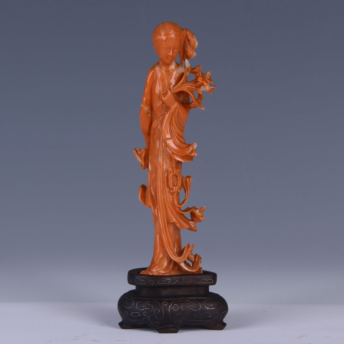 A RED CORAL CARVED BEAUTY STATUE/ WOODEN STAND