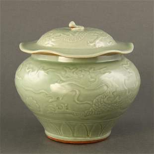 A CARVED CELADON 'DRAGON' JAR AND COVER